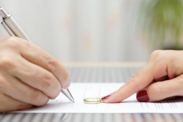 husband signing divorce agreement and woman push away weeding ri