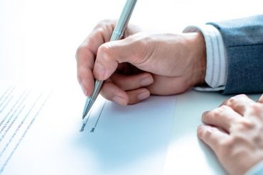 man signing post-nuptial agreement