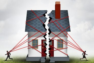 Broken family after a bitter divorce settlement and separation with a couple in a bad relationship breaking a house apart showing the concept of a marriage dispute and dividing assets